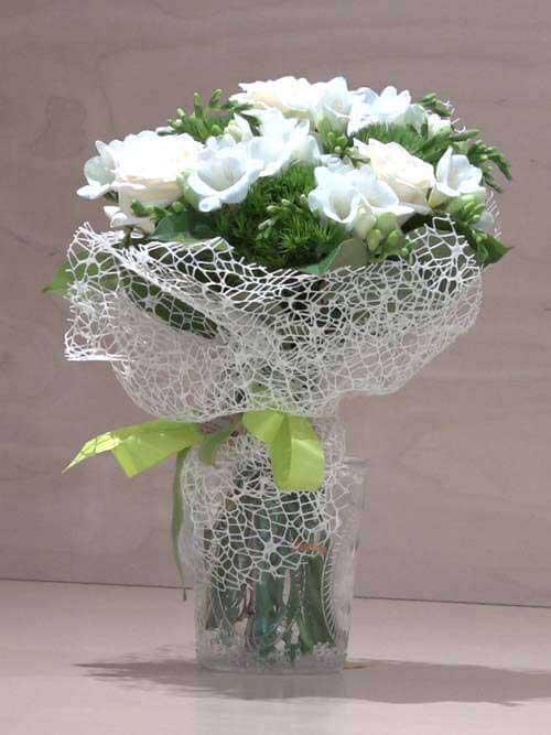 Mazzo di fiori bianco con fresie, roselline e garofano verde
